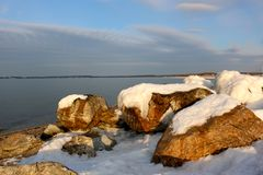Snow on rocky beach Royalty Free Stock Photos