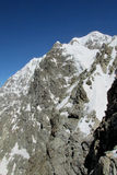 Snow and rocky mountain peak Stock Photos