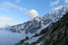 Snow and rocky peaks above the clouds Stock Photos
