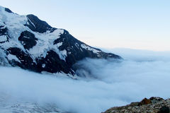 Snow and rocky peaks above the clouds Stock Image