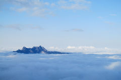Snow and rocky peaks above the clouds Stock Photography