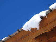 Snow on roof. Snow melting on roof at blue sky stock image