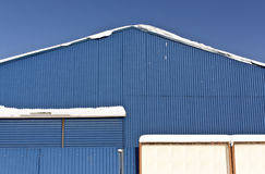 Snow on the roof of blue metal warehouse. Royalty Free Stock Photo