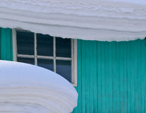 Snow on the roof of the house and a shed. Hanging a thick layer of snow. End of winter Stock Images