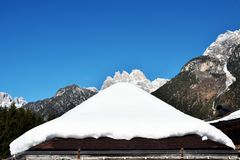 Snow on the roof during winter days, concept. Snow on a roof during winter days in Dolomiti mountains, in Italy. Concept and suggestion of the arrival of winter royalty free stock image