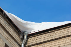 Snow on roof with winter gutter and icicles Royalty Free Stock Photography