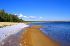 Snow, Sand, and Water, Big Bay State Park, Madeline Island, Apostle Islands, Wisconsin. Sunny Spring day on the sandy beach at Big Bay State Park on Madeline Royalty Free Stock Image
