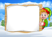 Snow Scene Landscape Christmas Elf Sign. Christmas elf cartoon character in winter snow scene landscape peeking around wooden scroll sign and giving a thumbs up Stock Photo