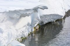 Snow and wind shaped sculpture over a stream stock photography
