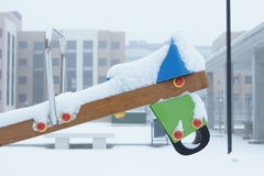 Snow on See-saw, Horse. Snow accumulated on a horse shaped see-saw in children's playground Stock Image
