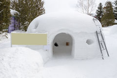 Snow shelter with blank yellow sign Royalty Free Stock Photo