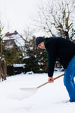 Snow shovel. Man shoveling snow in wintertime Royalty Free Stock Photography