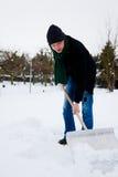 Snow shovel. Man shoveling snow in wintertime Royalty Free Stock Photo