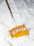 Snow shovel. Yellow snow shovel standing on the snow Royalty Free Stock Photo