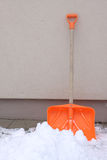 Snow shovel. Orange plastic snow shovel against building wall Royalty Free Stock Photos