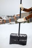 Snow shovel in female hands on a winter day Royalty Free Stock Photo
