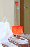 Snow shovel and front door Royalty Free Stock Photos