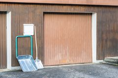 Snow shovel in front of a double garage without snow, Germany stock photo