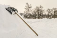 Snow shovel on a high snowdrift near countryside road royalty free stock image
