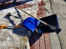 Snow shovel and ice ax in the snow against the background of a tile and fence in spring or winter stock photos
