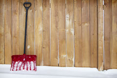 Snow shovel leaning agains a fence Royalty Free Stock Images