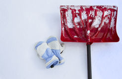 Snow shovel and mittens in snow Royalty Free Stock Photos