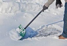 Snow Shovel pushing snow. A green snow shovel pushing snow Stock Photography