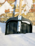 Snow shovel in the snow on a background of a brick wall Royalty Free Stock Photos
