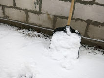 Snow shovel in the snow on a background of a brick wall. Snow shovel on a background of a brick wall Stock Photo