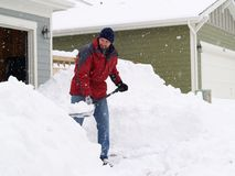 Snow shoveling. Man shoveling a lot of snow during a blizzard royalty free stock images