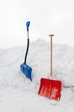 Snow Shovels. Multicolored snow shovels in snow pile Royalty Free Stock Images