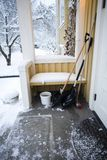 Snow showels. Showels and a brush waiting to be used on the porch of the house Stock Photography