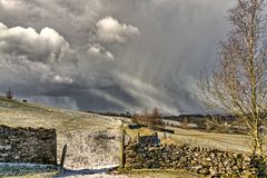 A snow shower falling in the North of England with a gate and dr Stock Image