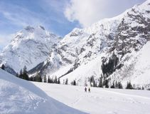 Snow, skiers and mountain backdrop Royalty Free Stock Photos