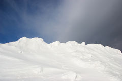 Snow and sky background. Snowdrift and particular winter sky in grey and blue tones with vaporous clouds Stock Photo