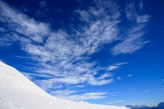 Snow, sky and clouds in the mountains Stock Photography