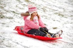 Snow sledding. Young girl has fun while traveling down hill on sled after the snow has fallen royalty free stock photography