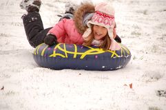 Snow sledding. Young girl has fun while sledding on freshly fallen snow on a hill in Illinois Stock Image