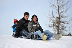 Three Latin Siblings Having Fun in the Snow on a C. Three children playing outside in winter time, they are going to slide down a steep hill and have fun, small Stock Image