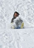 Latin Teenager Sliding Down a Snowy Steep Hill on Stock Photo
