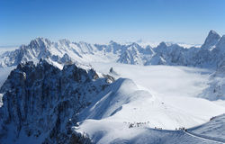 Snow slope with mountain-skiers, the Alps Stock Photos