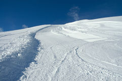 Snow slope at Val d'Isere. The border of the groomed snow slope at Val d'Isere, Espace Killy, France. Sunny winter day stock image