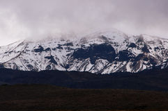 Snow slopes on Ruapehu. Snow sits on the lower slopes of Mount Ruapehu in New Zealand's north island National Park. The upper peaks hidden in cloud Royalty Free Stock Images