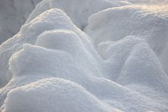 Snow snowbank on a Sunny day. Fluffy snow shimmers in the sun, abstract natural figures. Snow snowbank on Sunny day. Fluffy snow shimmers in the sun, abstract stock photos