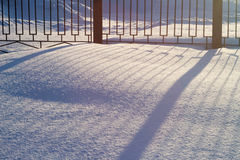 Snow is sparkles in sunny day and smooth shadow from beautiful fence. Royalty Free Stock Photography
