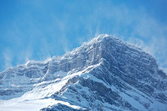 Snow spindrift on mountain peak 01. Snow blowing off top ridges of Mount Rundle in Banff National Park, Canada Stock Image