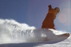 Snow splashes under snowboarder stock photo