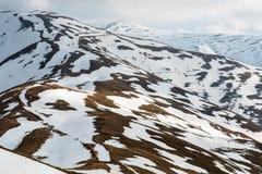 Snow spotted mountain slopes Royalty Free Stock Photos