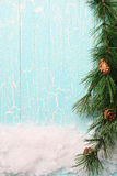 Snow and spruce branches on a wooden board painted Stock Photo
