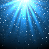 Snow and stars are falling on the background of blue luminous rays. Royalty Free Stock Images